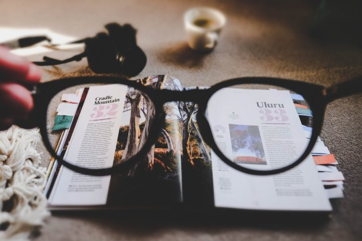 Glasses held above the book, Not knowing mind is always curious, Photo by Ewan Robertson.jpg