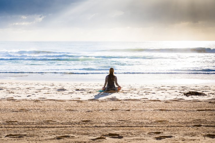woman meditating on the beach, photo by Simon Rae